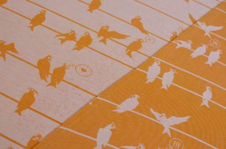 Tragetuch in Orangeton mit weißem Vogelmuster